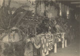 African American exhibit at a fair, featuring quilts, preserves, clothing, and baskets.