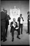[A. Philip Randolph, seated, and John Lewis, standing next to him looking into an envelope, with a group of men, in front of the statue of Abraham Lincoln at the Lincoln Memorial during the March on Washington]