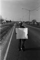 Woman carrying a protest sign during the 20th anniversary reenactment of the Selma to Montgomery March in Selma, Alabama.