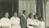 African American teachers standing on the porch of a brick school building, probably the Clarke School in Selma, Alabama.