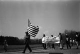 Man carrying an American flag during the 20th anniversary reenactment of the Selma to Montgomery March.
