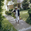 Hattie Dillard walking through a neighborhood, probably in Birmingham, Alabama, carrying baskets of vegetables she intends to sell.