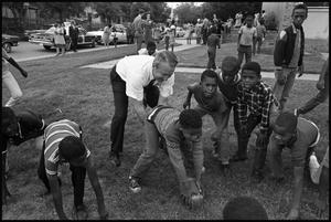 Photograph of Texas Attorney General Waggoner Car playing football with young students