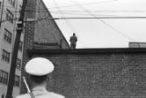 Police officer looking up at a man on the roof of a building after the bombing of 16th Street Baptist Church in Birmingham, Alabama.