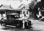 Man sitting on car playing banjo