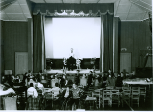 Photograph of Georgia Warm Springs Foundation patients and staff watching a live performance on the playhouse stage at the Georgia Warm Springs Foundation, Warm Springs, Meriwether County, Georgia, 1930-1940?
