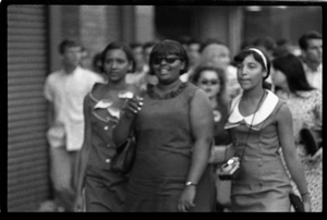 Beatles concert at Shea Stadium: three African American girls in a crowd of fans outside the stadium