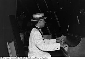 Photograph of the left side profile of an unidentified man playing a piano Jack Evans Breakfast with JBAAL