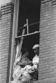 African Americans looking through a window that was blown out during the bombing of 16th Street Baptist Church in Birmingham, Alabama.