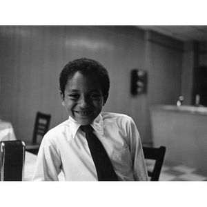 Young boy wearing a necktie and smiling.