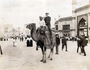 """""""A camel ride through the Pike."""" (White man riding a camel with an Egyptian driver in the Pike section of the 1904 World's Fair)."""