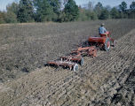 African American man on a red McCormick-Deering Farmall Cub tractor, plowing a field on Price McLemore's Oaks Plantation in Montgomery County, Alabama.