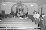 Small audience and camera crew in the auditorium of a church building, possibly after a civil rights meeting in Montgomery, Alabama.