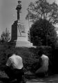 Young man and woman kneeling at the base of the Confederate monument in Tuskegee, Alabama, during a student demonstration to protest the verdict in the trial of Thomas Coleman, a Lowndes County man who had been charged with the murder of Jonathan Daniels.