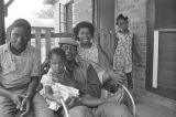 Jimmy Bates with children on the front porch of a brick house in Newtown, a neighborhood in Montgomery, Alabama.