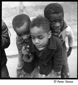 Group of three African American boys playing with a toy dart gun