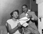 Autherine Lucy and Arthur Shores reading correspondence (possibly her acceptance letter) from the Office of Admissions and Records at the University of Alabama.