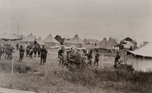 View of a black army band playing music amongst rows of tents in a German prisoners camp behind a barbed wire fence