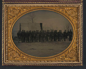 [Company H, 124th New York Infantry Regiment in winter camp in Virginia, possibly Brandy Station, posed in Union uniforms in front of a building]