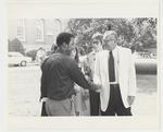 President Singletary is standing outside next to the cannon near the Administration Building. He is shaking hands with an unidentified male African-American student. Standing near President Singletary are two unidentified female students and one unidentified male student