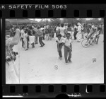 Two boys with invisible dog leashes as people dance at Watts Summer Festival, Calif., 1979