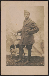 [Robert Bennett Smith in uniform, overcoat, and overseas cap, holding a chair in front of a backdrop]