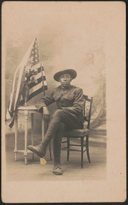 [Unidentified African American soldier in uniform and campaign hat sitting next to vase of flowers and American flag in front of painted backdrop]
